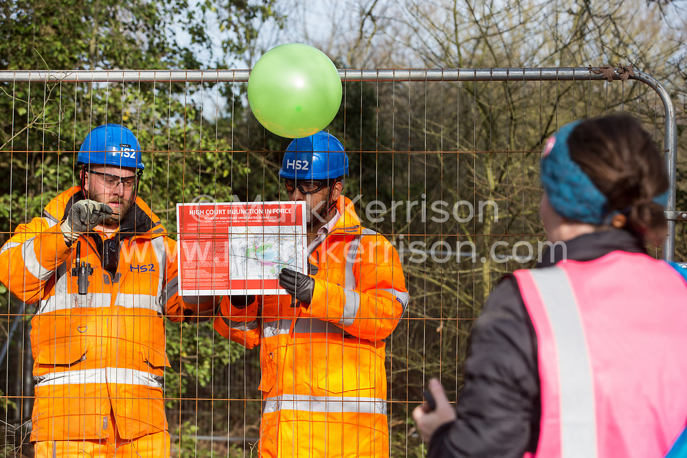 Harefield, UK. 7 February, 2020. HS2 engineers fix a High Court injunction notice to Heras fencing erected to surround three environmental activists from Extinction Rebellion who have climbed a veteran oak tree close to the Harvil Road wildlife protection camp in order to try to protect it from felling. HS2 are expected to try to fell large numbers of mature trees in the immediate vicinity over the weekend even though the high-speed rail link is still awaiting Boris Johnson's approval.