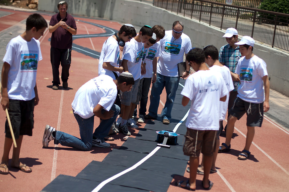 """Jewish Israeli youth watch as a small electric car they developed performs a task, during the final stages of The Gildor Family Projects and Inventions competition, at the Israel Center for Excellence through Education in Jerusalem on June 30, 2011. Teams of students from high schools across Israel and the U.S. participated in the competition which featured the topic of development of a """"smart"""" electric car, involving robotic elements, as the cars were required to perform several specific tasks. The project also addressed issues of alternative energy, with teams receiving a significant bonus for incorporating solar energy in their designs."""