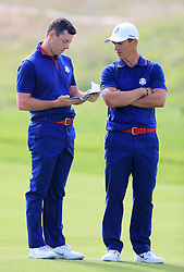 Team Europe's Rory McIlroy (left) and Thorbjorn Olesen check their scorecards during the Fourballs match on day one of the Ryder Cup at Le Golf National, Saint-Quentin-en-Yvelines, Paris.