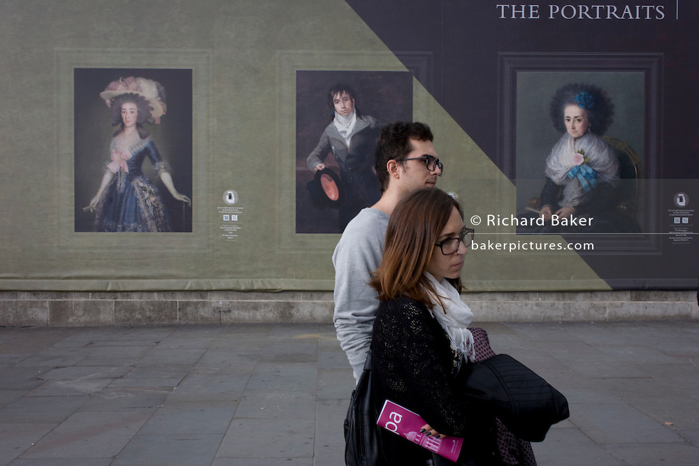 A tourist couple listen to a busker near Goya portraits, sponsored by Credit Suisse and advertised on a construction hoarding outside the National Portrait Gallery.