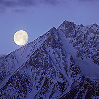 The moon sets over Basin Mountain on the eastern crest of California's Sierra Nevada.