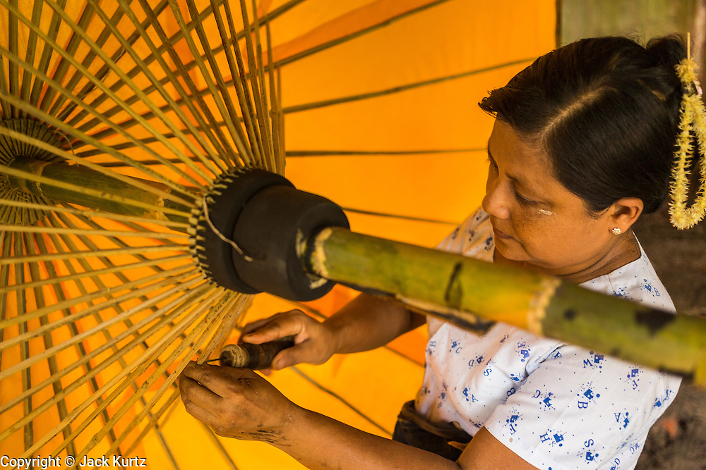 14 JUNE 2013 -  PATHEIN, AYEYARWADY, MYANMAR: A worker strings an umbrella at the Shwe Sar umbrella factory in Pathein. Pathein is a center of the Burmese umbrella and parasol industry. Most are actually parasols made in the traditional Burmese way using treated paper which is not water proof. Shwe Sar's umbrella's are made with treated cloth and are waterproof. Since US and European sanctions have been lifted businesses in Myanmar have seen an explosion in exports. Shwe Sar exports most of their umbrellas to Europe. Pathein, sometimes also called Bassein, is a port city and the capital of the Ayeyarwady Region, Burma. It lies on the Pathein River (Bassein), which is a western branch of the Irrawaddy River. It's the fourth largest city in Myanmar (Burma) about 190 km west of Yangon.   PHOTO BY JACK KURTZ