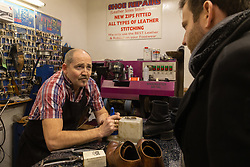 Shoe repair and key cutter Martin, 52, left, talks with Bild journalist Philip Fabian about Brexit in his Charing Cross shop in London. London, January 16 2019.