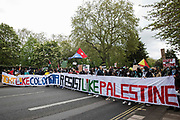 Protesters walk behind banners reading Fight Like Colombia Resist Like Palestine during a Free Palestine SOS Colombia solidarity march from the Colombian embassy to the Israeli embassy on 15th May 2021 in London, United Kingdom. Speakers at a rally before the march, which took place on Nakba Day, highlighted human rights abuses being directed against Palestinians in Israel and the Occupied Territories, in particular attempts at forced displacements in Sheikh Jarrah in East Jerusalem, and also in Colombia, where peaceful demonstrators and human rights defenders have been killed and subjected to repression, detention and torture.