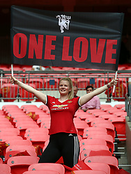 Manchester United fan holds up a 'One Love' flag prior to kick-off