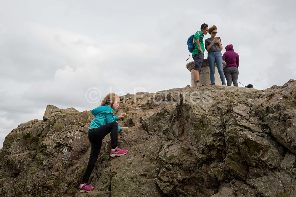 A young girl climbs the last feet of granite at the summit of The Beacon, on 15th September 2018, in Malvern, Worcestershire, England UK. Worcestershire Beacon, also popularly known as Worcester Beacon, or locally simply as The Beacon, is a hill whose summit at 425 metres 1,394 ft[1] is the highest point of the range of Malvern Hills that runs about 13 kilometres 8.1 mi north-south along the Herefordshire-Worcestershire border, although Worcestershire Beacon itself lies entirely within Worcestershire.
