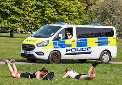 © Licensed to London News Pictures. 16/04/2020. London, UK. Two women exercise on a warm Spring day as Police vans patrol Primrose Hill enforcing lockdown rules on social distancing and exercise. Meanwhile, Pret A Manger and other coffee shops in London start to reopen and Ministers consider when and how the lockdown will finish as politicians are warned that the UK could face the worst recession in 300 years. Photo credit: Alex Lentati/LNP