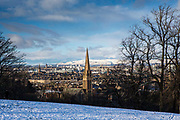 The sandstone spire of Queen's Park Baptist Church taken from Queens Park. The park is known for its view across the south side of Glasgow, with a snow covered Campsie Fells in the background.