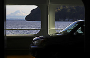 Mount Rainier offers a last glimpse before coming rains, as a passenger reads in his car on a ferry run from Vashon Island to West Seattle. (Ken Lambert / The Seattle Times)