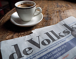 Detail of Dutch newspaper and coffee cup in typical brown cafe in Utrecht in The Netherlands