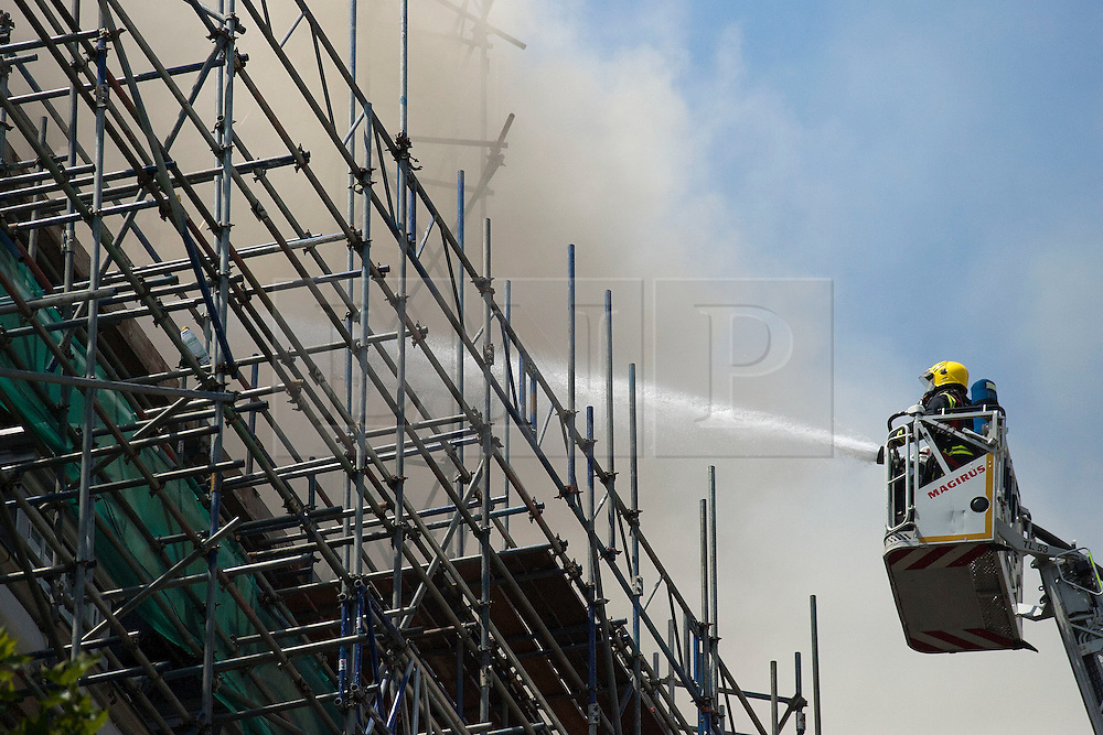 © Licensed to London News Pictures. LONDON, UK  14/06/11. A firefighter hoses down flames breaking through the roof of a building on Aldwich in London today (Tuesday). The incident in the building, which was under renovation at the time, saw 15 fire engines and 75 firefighters work to control the fire. Please see special instructions for usage rates. Photo credit should read Matt Cetti-Roberts/LNP