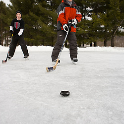 Boys playing hockey on a frozen pond in Quechee, Vermont.