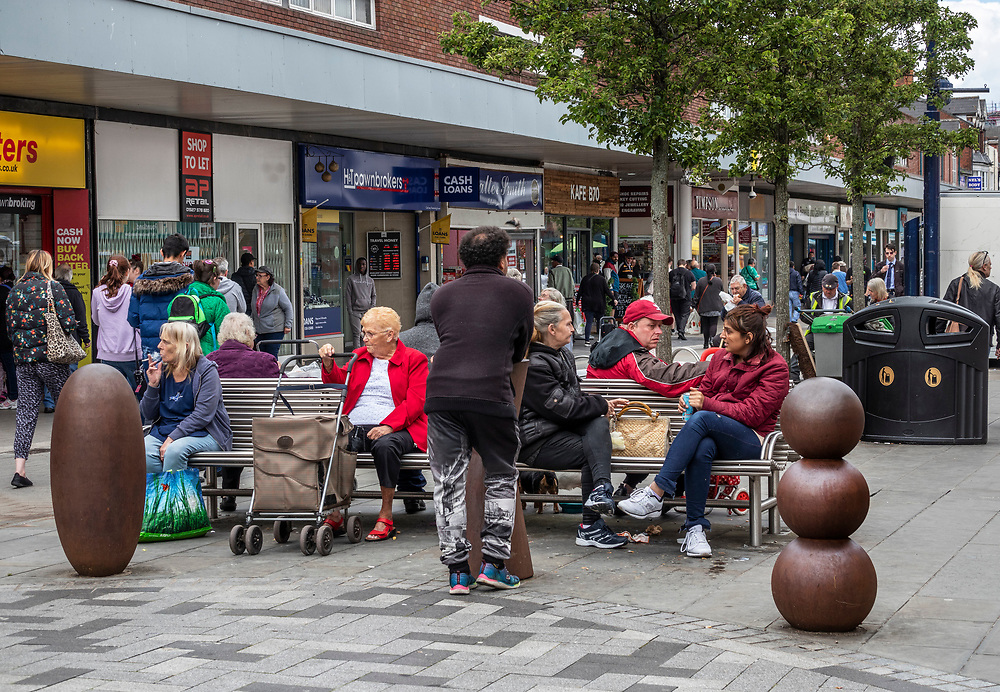 Local shoppers on the High Street, West Bromwich, West Midlands, UK. With shop to let in background.