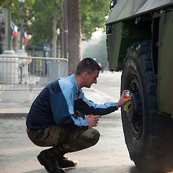 Soldat de l'armée de terre préparant au cirage les pneus de son véhicule sur l'avenue des Champs Elysées à l'occasion des célébrations de la fête nationale.<br /> 14 juillet 2013, Paris (75)