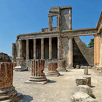 Part view of the Basilica with the elegant Hellenistic styled two-level Tribunal in the background at Pompeii Italy.  Dating back to the 2nd century BC, the basilica is the oldest public building in the city. It was originally a covered market and then became the seat of the Law Courts at the beginning of the 1st century AD. It was then that the Tribunal was built at the west end of the building. The surrounding portico consisted of 28 fluted Corinthian column reaching 11 metres in height.