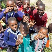 Children excitedly give the thumbs up at Giwa Resettlement Farm near Nakuru in Kenya's Rift Valley Province.