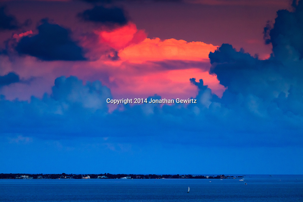 Billowing summer clouds over the southern tip of Key Biscayne, Florida reflect red light from the setting sun.<br /> <br /> WATERMARKS WILL NOT APPEAR ON PRINTS OR LICENSED IMAGES.