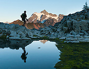 A hiker reflects in a mountain tarn (pond). Mount Shuksan (9127 feet elevation, located in North Cascades National Park) is seen from Heather Meadows, Mount Baker - Snoqualmie National Forest, Washington, USA.