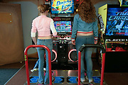 Two girls get ready to play an electronic dancing game at an amusement arcade at Alton Towers