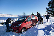 Fellow drivers try to dig out a car stuck in snow near Stow in the Scottish Borders on the 25th of January 2021, Scotland, United Kingdom. It has been snowing the previous day and the wind has created unforeseeable snow drifts on the windy country roads leading into Stow. The car was eventually pulled out by the drivers husband who turned up in their tractor.