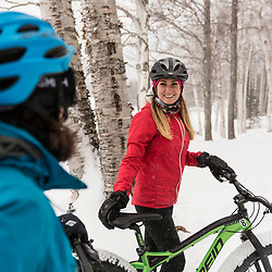Two women fat tire biking on a snowy winter day in New Hampshire's White Mountains.