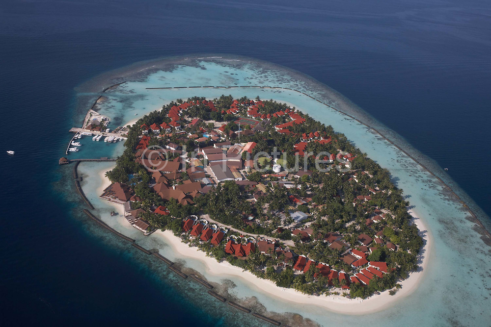 An aerial view of an unidentified island community seen from a regional aircraft passing overhead atolls and islands, a few miles to the north Malé, capital of the Indian Ocean Republic of the Maldives. We see the perfectly clear blue sea surrounding an island of white coral beach sand, a harbour, holiday apartments and importantly coastal defence barriers that may defend against rising sea levels as global warming makes sea level locations like this vulnerable to flooding. The Maldives comprise of twenty-six atolls, featuring 1,192 coral islands of which 80 are holiday resorts with 200 inhabited by indigenous communities. This Islamic nation of 298 sq km (115 sq miles), lie seven hundred kilometres (435 miles) south-west of Sri Lanka.