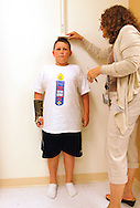 Zachary Frantzen, 10, (L) is measured by Marilyn Day director of the Shapedown Program at The Children's Hospital in Aurora, Colorado July 8, 2010.  The program is part of the child and teen weight management program at the hospital. REUTERS/Rick Wilking (UNITED STATES)