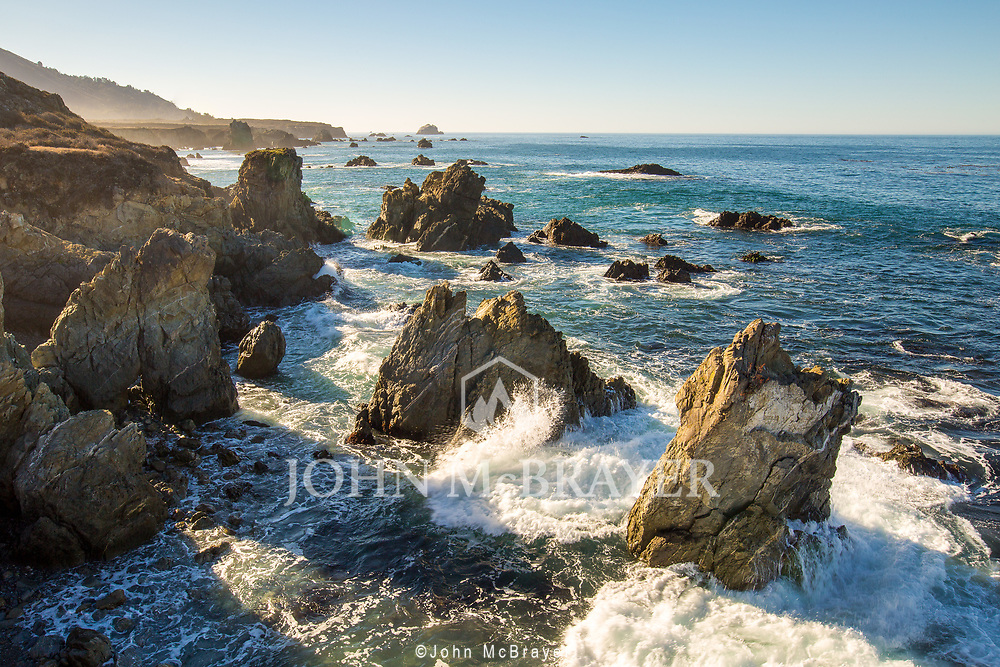 Morning sun peering over the hills as the waves break on the rocks in Big Sur, CA. © John McBrayer2015