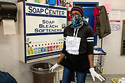 "Brooklyn, NY - 6 April 2020, An attendant at a laundromat in Brooklyn's Midwood neighborhood, and protected with a face mask and latex gloves, wears a sign that reads ""Keep Back / 6 Feet"" to remind patrons of social distancing standards. Laundromats are among the businesses deemed to be essential services, although some have closed for the outbreak."