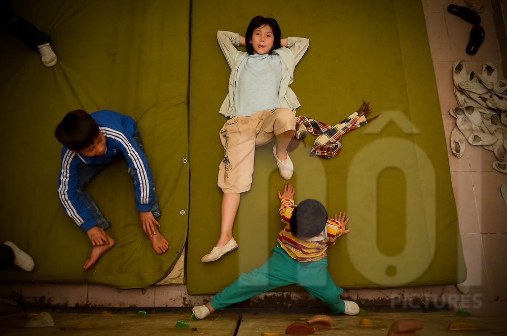 Three boys relax on the climbing wall safety mattress in Nguyen Viet Xuan school in Hanoi, Vietnam, Southeast Asia, as part of the Ta Ke project.