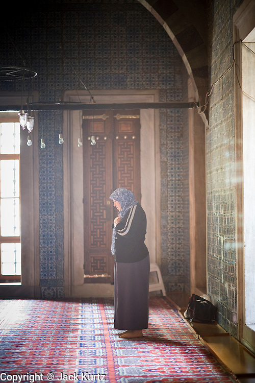 """08 AUGUST 2007 -- ISTANBUL, TURKEY: A woman prays in the """"Yeni Camii"""" (New Mosque) in Istanbul, Turkey. Turkey is a secular country but well over 90 percent of the population is Moslem. Istanbul, a city of about 14 million people, and the largest city in Turkey, straddles the Bosphorus Straits between Europe and Asia. It is one of the oldest cities in the world. It was once the center of the Eastern Roman Empire and was called Constantinople, named after the Roman Emperor Constantine. In 1453, Mehmet the Conqueror, Sultan of the Ottoman Empire, captured the city and made it the center of the Ottoman Turkish Empire until World War I. After the war, the Ottoman Empire was dissolved and modern Turkey created. The capitol was moved to Ankara but Istanbul (formerly Constantinople) has remained the largest, most diverse city in Turkey.    Photo by Jack Kurtz"""