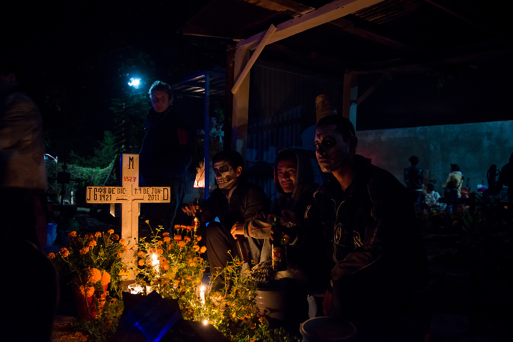"""During Day of the Dead celebrations (""""Día de los Muertos"""" in Spanish), young men sit beside a loved one's grave at the cemetery in Xoxocotlán, on the outskirts of Oaxaca, Mexico."""