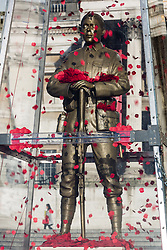 © Licensed to London News Pictures. 07/11/2014. London, UK. The Every Man Remembered First World War sculpture by artist, Mark Humphrey, is unveiled by the Royal British Legion in Trafalgar Square, central London today. The brass sculpture, loosely based on the Unknown Solider, stands on a plinth of limestone sourced from the Somme and is encased in a Perspex obelisk, surrounded by poppies which float up around the figure every five minutes. Photo credit : Vickie Flores/LNP