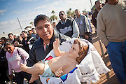 """Dec. 12, 2009 -- PHOENIX, AZ: A woman carries a doll representing baby Jesus during a procession to honor the Virgin of Guadalupe at St. Catherine of Siena Catholic Church in Phoenix, AZ. Most of the members of the church are Hispanic and Dec. 12, Virgin of Guadalupe Day, is one of the church's most important holy days. The Virgin of Guadalupe appeared to Juan Diego, a Mexican peasant, on Dec 9, 1531, on a hillside near Mexico City. She is the """"Queen of Mexico"""" and """"Empress of the Americas"""" and revered throughout Latin America.  Photo by Jack Kurtz"""
