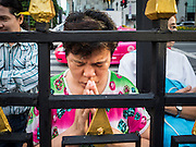 "04 SEPTEMBER 2015 - BANGKOK, THAILAND: People who couldn't get into the shrine Friday morning pray in front of Erawan Shrine during a special rededication ceremony. A ""Holy Religious Ceremony for Wellness and Prosperity of our Nation and Thai People"" was held Friday morning at Erawan Shrine. The ceremony was to regain confidence of the Thai people and foreign visitors, to preserve Thai religious customs and traditions and to promote peace and happiness inThailand. Repairs to Erawan Shrine were completed Thursday, Sept 3 after the shrine was bombed on August 17. Twenty people were killed in the bombing and more than 100 injured. The statue of the Four Faced Brahma in the shrine was damaged by shrapnel and a building at the shrine was damaged by debris.     PHOTO BY JACK KURTZ"