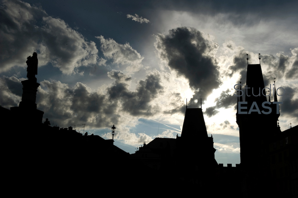Two Bridge towers and a statue of Charles Bridge are seen as silhouettes against the light, in Prague, Czech Republic, on August 15, 2011. Photo by Lucas Schifres/Pictobank