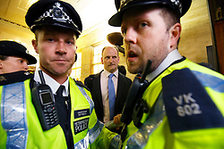 © Licensed to London News Pictures. 27/05/2015. Westminster, UK. Police officers guarding UKIP MP Douglas Carswell, who is surrounded by demonstrators taking part in an End Austerity Now protest outside St James's Tube station in London. Activists are demonstrating against the current conservative government and planned spending cuts. At a previous demonstration by the same group  a war memorial on Whitehall was defaced. Photo credit: Tolga Akmen/LNP