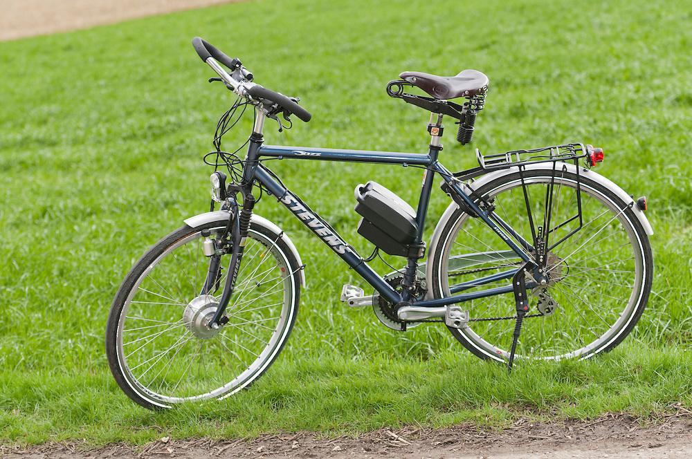 Elektrofahrrad an einem Feldweg geparkt vor grünem Acker Germany, an e-bike standing in front of a green arable field