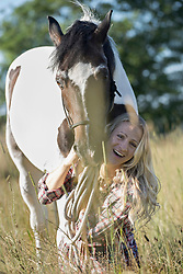 Mid adult woman holds her horse on leash on meadow and smiling, Bavaria, Germany