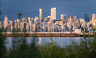 Sunset lights up the skyline architecture of Vancouver, British Columbia as seen from across the water at Jericho Beach Park