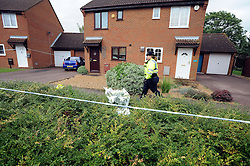 © licensed to London News Pictures. Wallingford, UK.  06/09/11.A police woman walks past a bunch of flower left outside an address cordoned off by police. Thames Valley Police have launched a murder investigation today, in Walnut Tree, Milton Keynes, after a man was found with fatal injuries last night (5/9/11). A 33 year old man was taken to Milton Keynes General Hospital but died from his injuries a short time later. A second man aged 32 has been arrested. Mandatory Credit Stephen Simpson/LNP