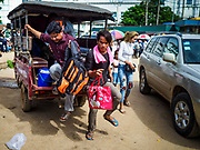 05 JULY 2017 - POIPET, CAMBODIA: Cambodian migrant workers in Poipet headed for Thailand get out of a tuk-tuk (three wheeled taxi) at the Thai-Cambodian border. The Thai government proposed new rules for foreign workers recently. The new rules include fines of between 400,000 and 800,00 Thai Baht ($12,000 - $24,000 US) and jail sentences of up to five years for illegal workers and people who hire illegal workers. Hundreds of companies fired their Cambodian and Burmese workers and tens of thousands of workers left Thailand to return to their countries of origin. Employers and human rights activists complained about the severity of the punishment and sudden implementation of the rules. On Tuesday, 4 July, the Thai government suspended the new rules for 180 days and the Cambodian and Myanmar governments urged their citizens to stay in Thailand, but the exodus of workers continued through Wednesday.     PHOTO BY JACK KURTZ