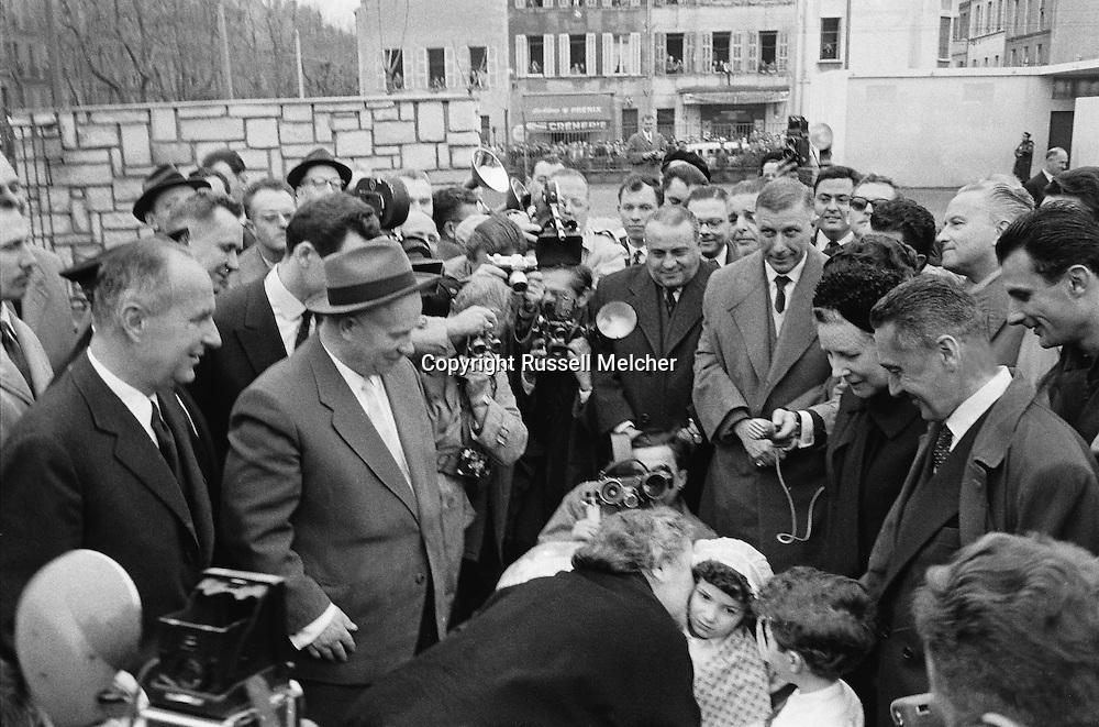 Mrs Khrushchev kisses little girl who is presenting flowers to President Khrushchev in Marseille, France.