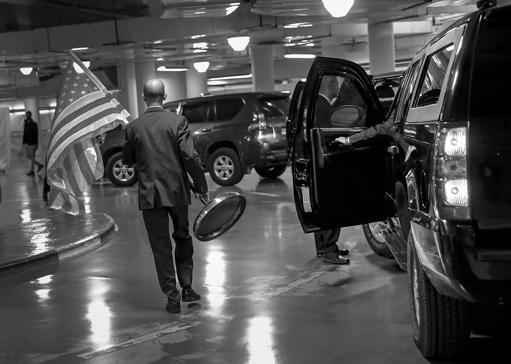 A staff member from the U.S. Embassy carries a flag through a parking garage in Jerusalem, Israel.