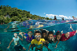 Over / under view of kids from Jan Village, Pulau Pura, who grow up in and around the water, and love to pose for underwater photos. Alor Region, Indonesia