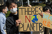 """A young Japanese man takes part in the Global Strike for Future at the United Nations University, Shibuya, Tokyo, Japan.Friday March 15th 2019. Part of a global day of action in 98 countries and nearly 2,000 cities; this was Japan's second Fridays for Future event, known as """"School strikes"""", and took place from 2pm to 4pm with activists and students holding signs demanding leaders, internationally and nationally, take measures to reduce ecologically damaging activities. The movement was started in 2018 by Swedish schoolgirl, Greta Thunberg, who began striking from her lessons when she realised that adult leaders were doing nothing to ensure there would be the future she was studying for."""