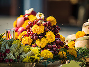 """19 DECEMBER 2016 - BANGKOK, THAILAND: Bees buzz around fruit left as an offering during the """"Spirit Appeasing"""" Ceremony held for the Royal Chariots at the Bangkok National Museum. The chariots will be used to take the body of Bhumibol Adulyadej, the Late King of Thailand, and members of the Royal funeral cortege to the cremation site on Sanam Luang for His Majesty's cremation. This will be the first cremation of a Thai King since 1950, when King Bumibol's brother, Rama VIII, Ananda Mahidol, was cremated. The design of the royal crematorium is based on Buddhist cosmology, with the main peak of Mount Sumeru (also known as Meru in Hindu cosmology) at center and eight other peaks signifying the levels of the universe. The crematorium will be decorated with mythical creatures such as garuda, angels, and Himmapan Forest creatures. The structure and funeral pyre will stand just over 50 meters tall. The exact date of the King's cremation has not been set yet but is expected to be late next year.     PHOTO BY JACK KURTZ"""