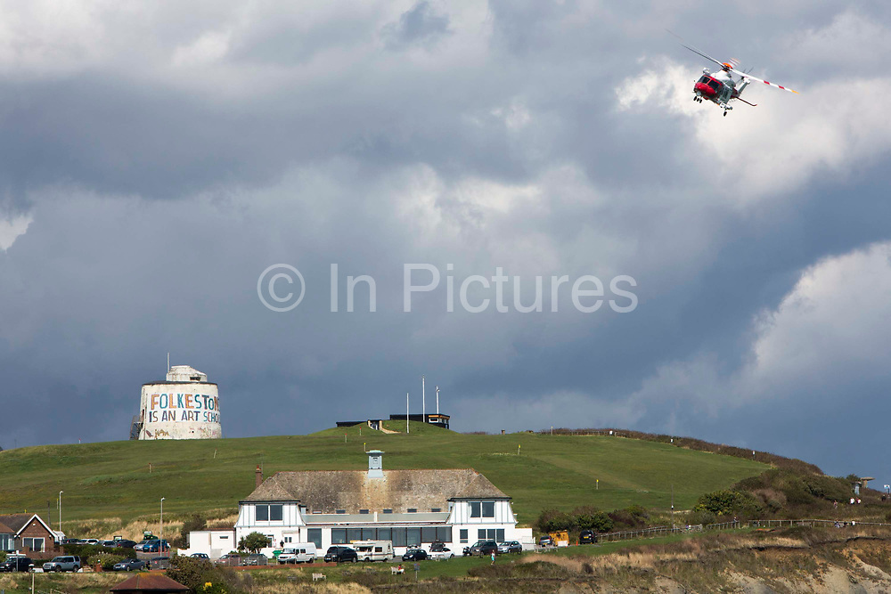 The HM Coastguard rescue helicopter G-C1JW  flying over the Folkestone is an Art School banner, attached to Folkestone's most prominent Martello Tower on the east cliff. The banner has been designed by the artist Bob and Roberta Smith as part of the 2017 Folkestone Triennial. Folkestone, Kent.