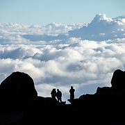 Four hikers are silhoutted against the clouds far below from Lava Tower (15,215 feet) on Mt Kilimanjaro's Lemosho Route.