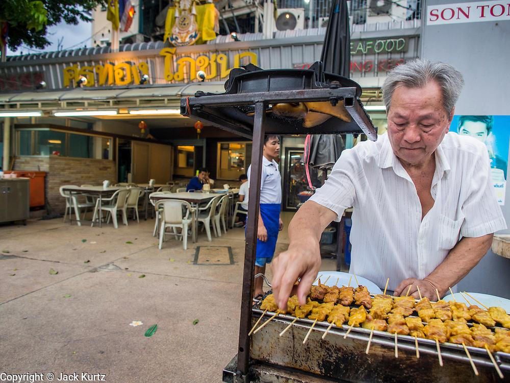 15 JULY 2014 - BANGKOK, THAILAND: A worker grills chicken satay at Sornthong Seafood Restaurant on Rama IV in Bangkok. Sornthong Seafood is a Thai-Chinese style restaurant.    PHOTO BY JACK KURTZ